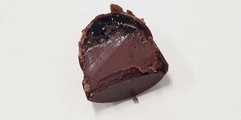 A filled chocolate cut in half, to evaluate the filling inside